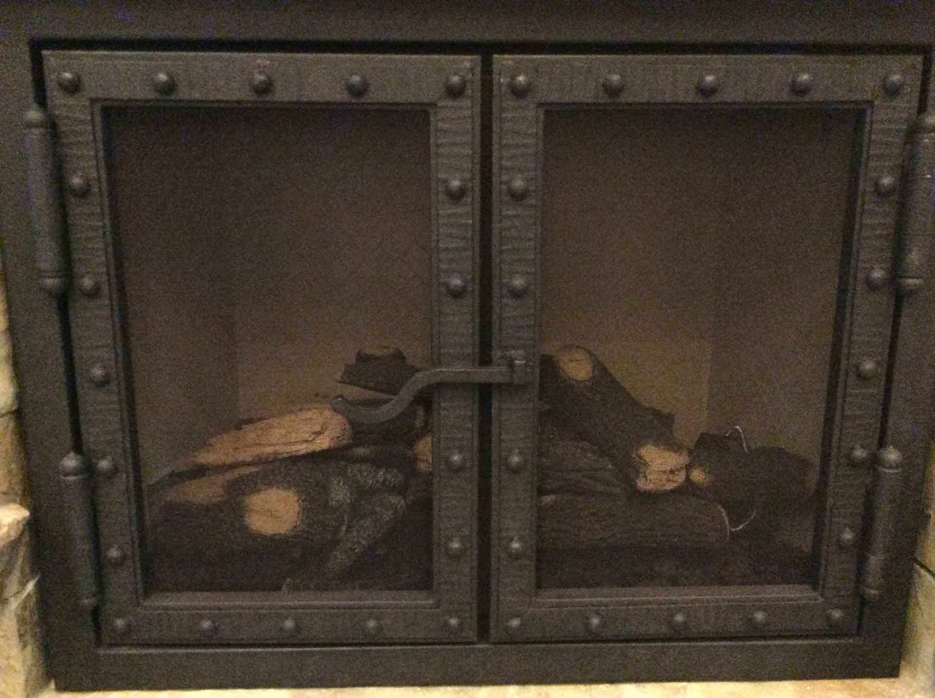 wrought iron fireplace screen with latch and rivets